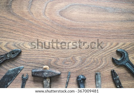Different tools (pliers, hammer, wrench, nippers, chisel, rasp, screwdriver) on a wooden background. Fathers day card with copy space. - stock photo