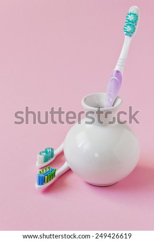different toothbrushes in a bowl on a colored background. care and hygiene of teeth. copy space background - stock photo