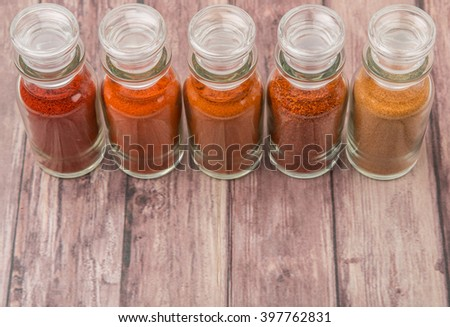 Different type and colors of chilly powder, paprika powder, cayenne powder in glass vial over wooden background - stock photo