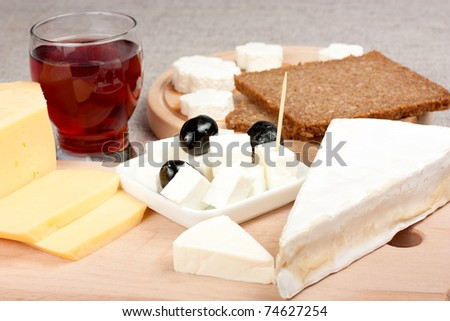 Different type of cheese and one glass of wine - stock photo