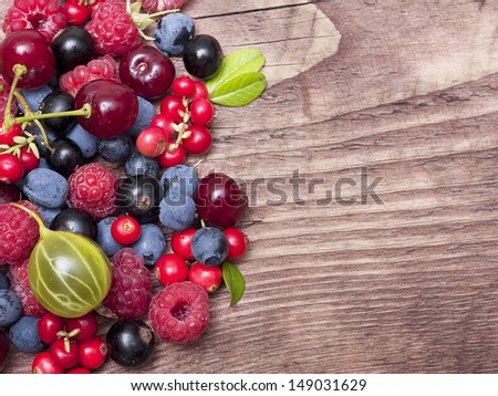 Different type of wild berry fruits on wooden background.
