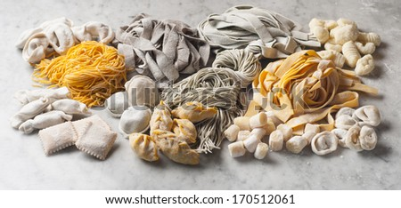 different types and flavors of fresh pasta on marble table - stock photo