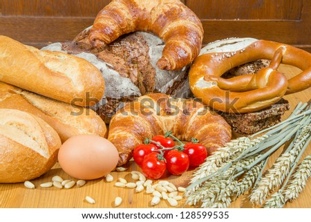 Different types of bakery products such a a loaf of bread, pretzel, whole grain bread and buns as well as tomatoes