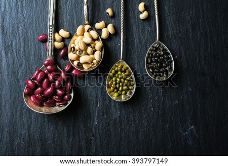 Different types of beans in the vintage spoons on the black stone background - stock photo