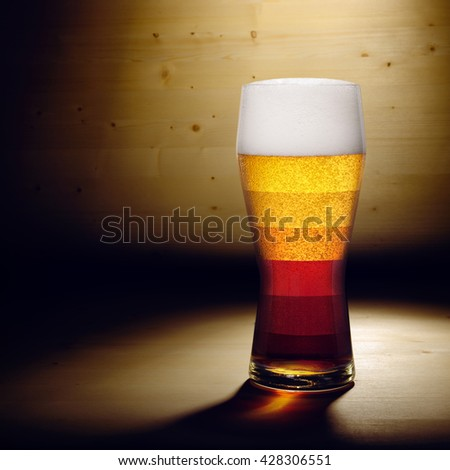 Different types of beer shown in one glass on wood background