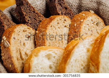 Different types of bread in the basket on the table in the interior of the restaurant - stock photo