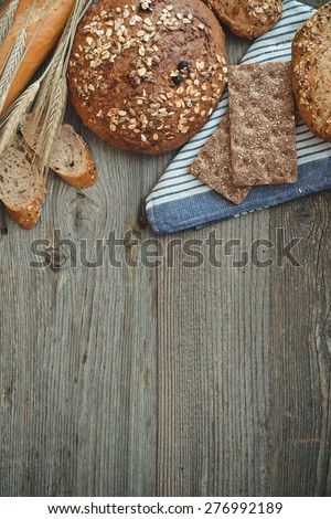 Different types of bread on a wooden table with ears of wheat - stock photo