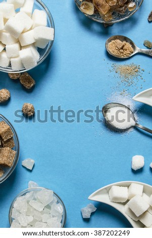Different types of brown and white sugar. On a blue table.