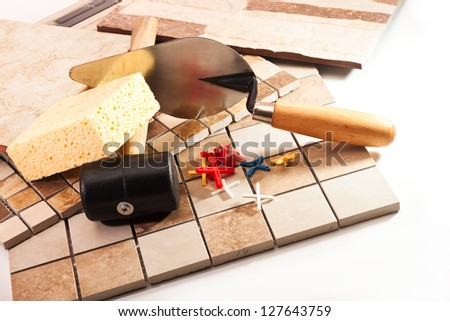 Different types of ceramic tiles, trowel, a rubber mallet, the crosses on a white background - stock photo