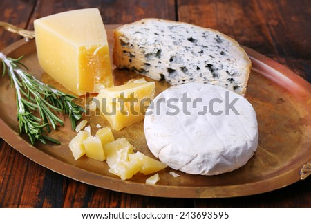 Different types of cheese on metal tray and wooden table background - stock photo