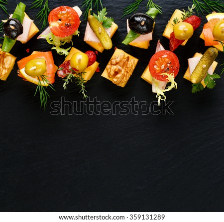 Different types of cheese skewers on a dark background. Delicious snack - stock photo