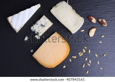 Different types of cheeses on black board with nuts. - stock photo