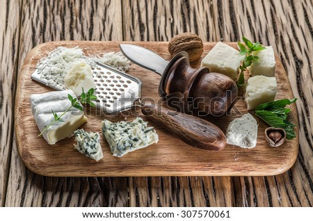 Different types of cheeses with nuts and herbs. Top view. - stock photo