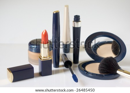 Different types of cosmetics and brush on light background. Shallow DOF (lipstick, brush). - stock photo