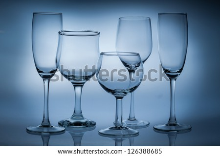 Different types of empty glasses on a blue background - stock photo