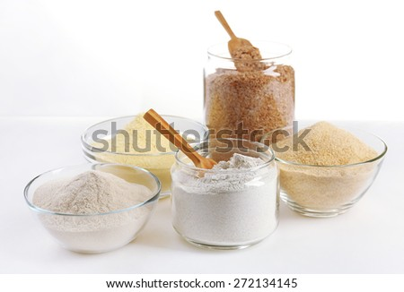 Different types of flour in bowls isolated on white - stock photo