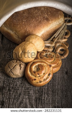 Different types of fresh bread and wheat ears on old wooden table. Toned.
