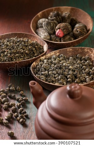 different types of green tea in bowls, a teapot on a wooden background (dark) - stock photo