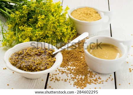 Different types of mustard: Dijon mustard and Russian, grain and mustard powder, mustard blossoms on a white wooden table. Selective focus - stock photo