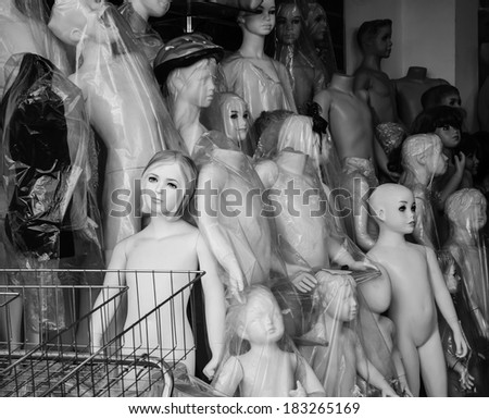 "Different types of naked mannequins for sale. Metaphor of alienation, estrangement and break up of the people in modern ""plastic"" world. Aged photo. Black and white. - stock photo"