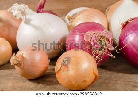 Different types of onions on wooden background