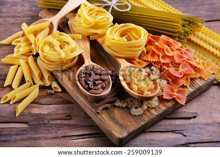 Different types of pasta on cutting board and wooden table background - stock photo