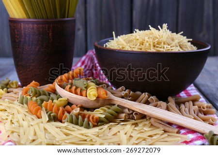Different types of pasta on napkin on wooden background