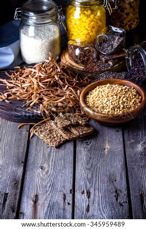 Different types of pasta, rice, peas,seeds of flax and chia on dark wooden table. Style rustic, selective focus. - stock photo