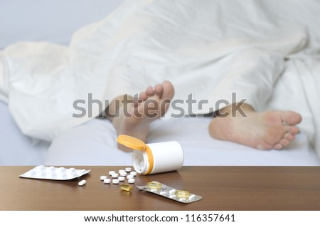 Different types of pills on the table. Person sleeping in the background.