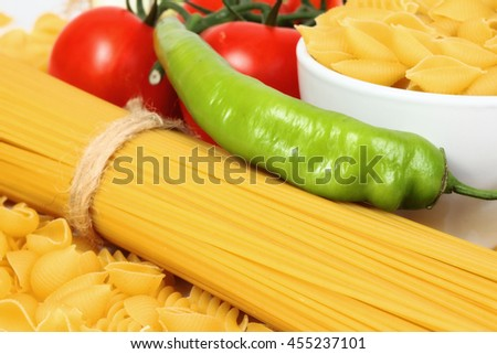 Different types of raw Italian pasta with tomatoes and other vegetables. Top view background.