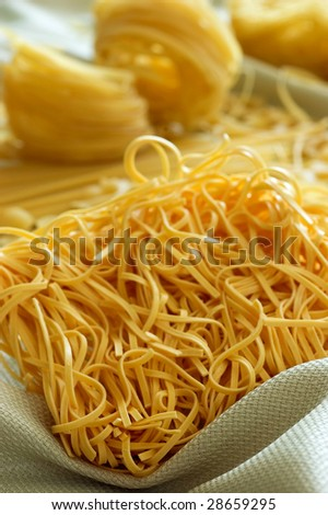different types of raw pasta on a tablecloth