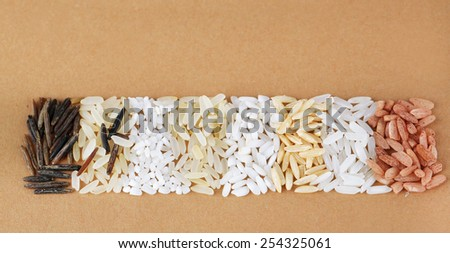 different types of rice on brown background - stock photo