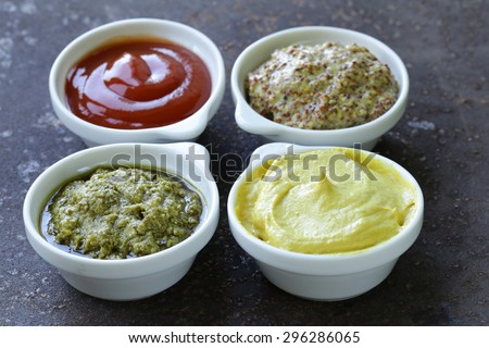 different types of sauces - ketchup, mustard, pesto - stock photo