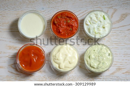 different types of sauces on wooden table - stock photo