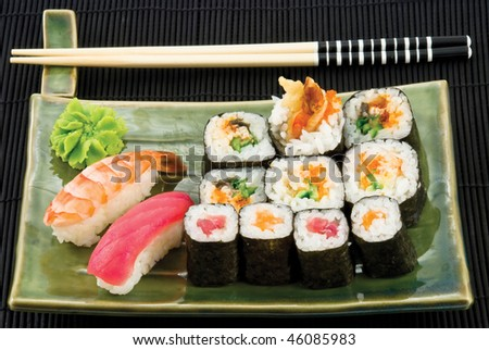 Different types of sushi in the plate isolated on black background with chopsticks