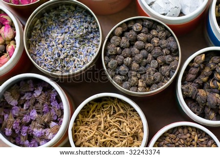 Different types of tea in round containers - stock photo
