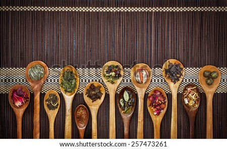 Different types of tea in wooden spoons - stock photo