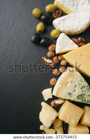 Different varieties of cheese on a black board - stock photo