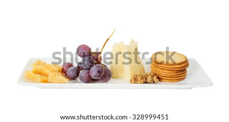 Different varieties of cheese, walnuts, red grapes and crackers on the white porcelain rectangular plate, isolated on white background - stock photo