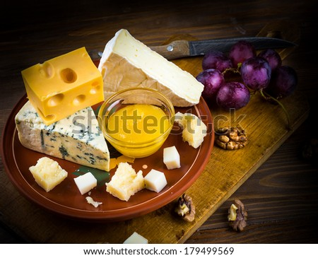 Different varieties of cheese with walnuts and grapes