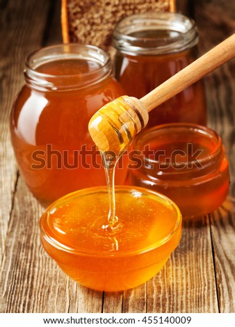 Different varieties of honey in a glass on the old board
