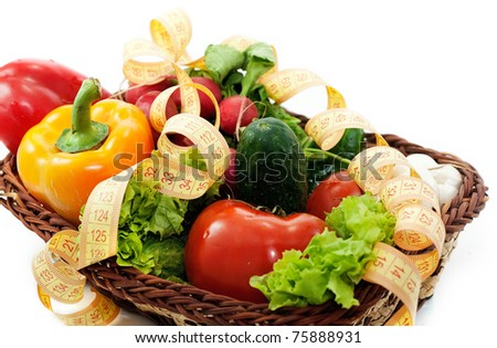 Different vegetables in a basket tied with a measuring tape - stock photo