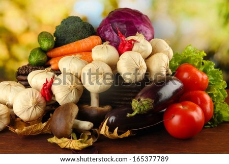 Different vegetables on basket with yellow leaves on table on bright background - stock photo