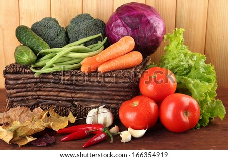 Different vegetables on basket with yellow leaves on table on wooden background - stock photo