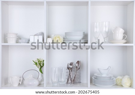 Different white clean dishes on wooden shelves - stock photo