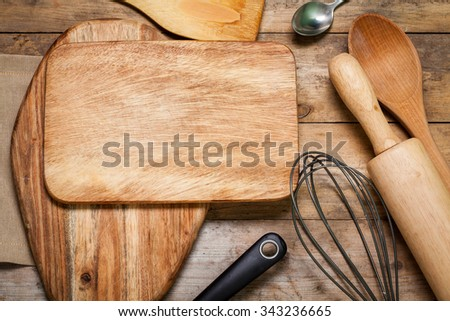Different wood kitchen tools on the old wood kitchen cutting board with textured paper background - stock photo