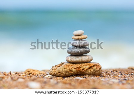 Differently sized and colored pebbles stacked, the sea in the background - stock photo