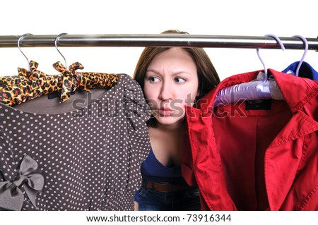Difficult choice. The young woman chooses clothes in a case - stock photo