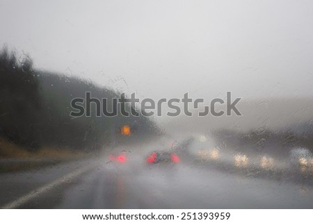 Difficult driving conditions - view through rain on windscreen - UK motorway - stock photo