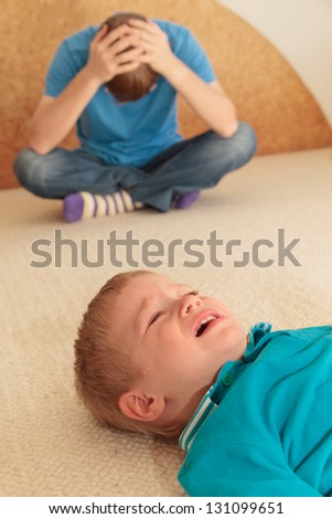 difficult parenting -child is crying, father is tired